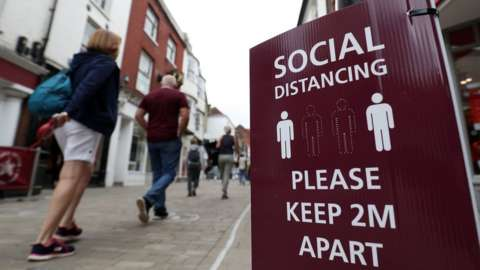 People walk past a social distancing sign