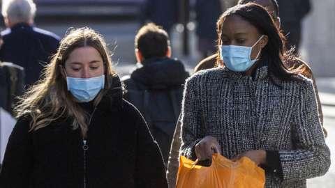 Two women wearing face masks walk along a street in London, on 21 October 2021