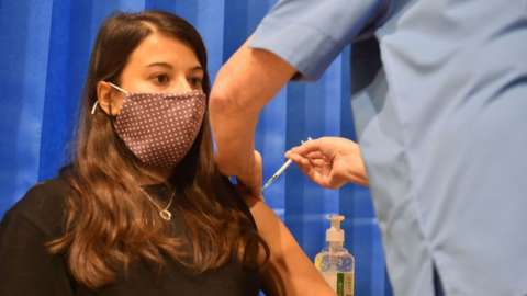 Lara Jesani, 26, from Cardiff, receives the first of two Pfizer-BioNTech Covid-19 vaccine on 8 December