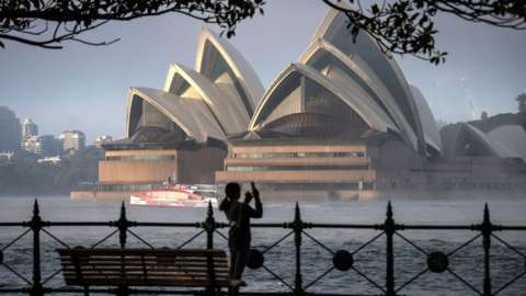 A woman takes a picture of the Sydney Opera House and Sydney Harbour