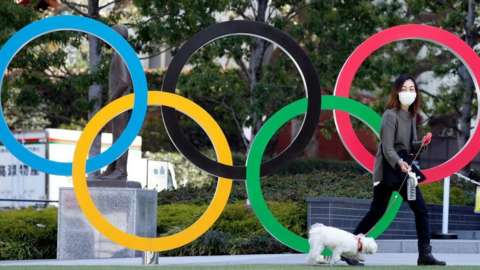Woman with dog in front of Olympic rings. File photo