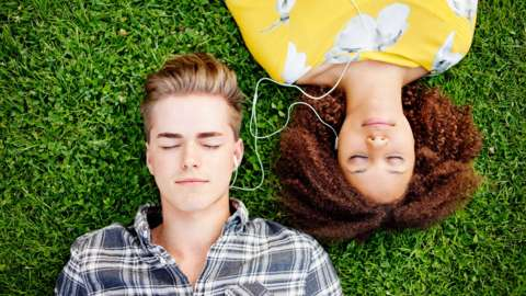A young man and woman recline on the grass with headphones