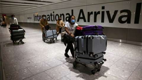 Travellers walk through the arrivals area at Heathrow Airport