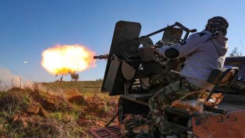 A Turkey-backed Syrian fighter fires a lorry-mounted gun in Idlib. Photo: February 2020