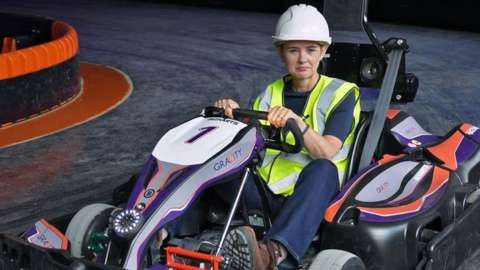 BBC Business Correspondent Emma Simpson tries out go-karting on a track in a former Debenhams beauty hall