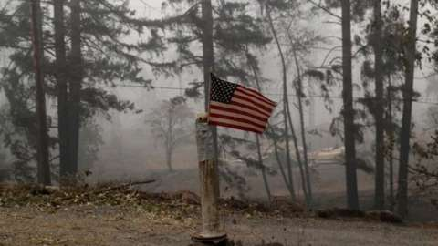 A U.S. flag is taped to the pole at the entrance of a house destroyed by fire in the aftermath of the Beachie Creek fire near Gate