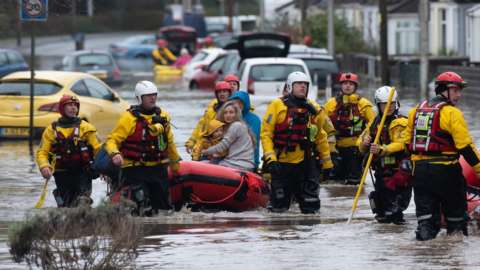A family is rescued from floodwater in Nantgarw by boat