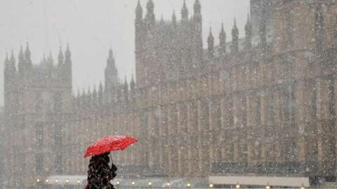 Woman crossing Westminster Bridge during snowstorm last month