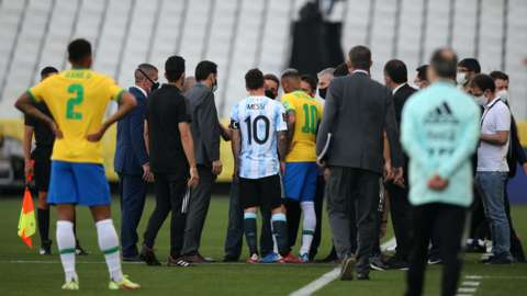 Lionel Messi and Neymar talk with officials after Brazil v Argentina is abandoned