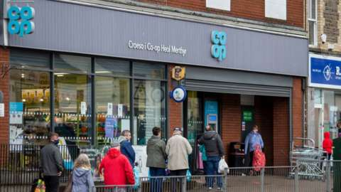 Customers queue outside a Co-op convenience store in Cardiff, Wales
