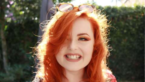 Close up of Lucy Edwards outside with red hair and eyeshadow wearing sunglasses on her head