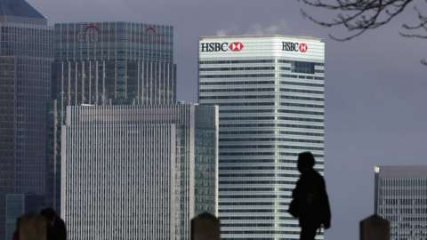 A man silhouetted against the HSBC headquarter in the Canary Wharf