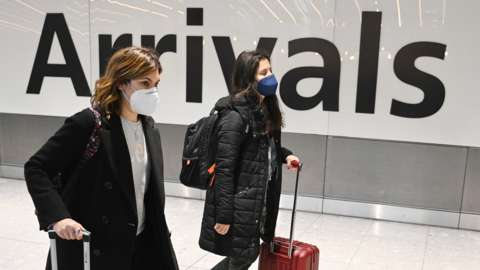 Travelers in the international arrival area of Heathrow Airport near London