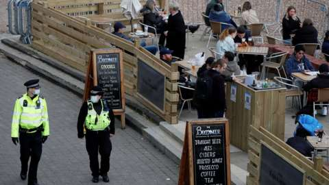 Police officers walk pass the terrace of a bar where people drink in Brighton after restrictions were eased on 12 April
