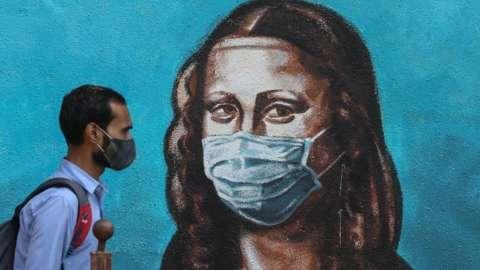 An Indian man walks past a wall showing a graffiti of Italian artist Leonardo da Vinci's Mona Lisa wearing a face mask, in Mumbai, India, 17 March 2021.