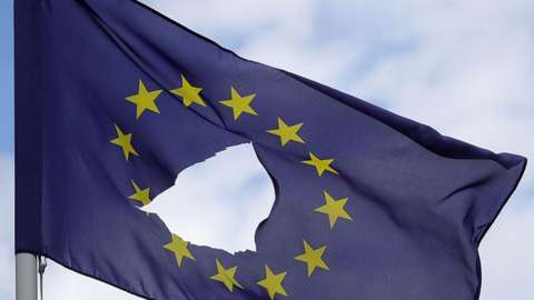 A European Union flag, with a hole cut in the middle
