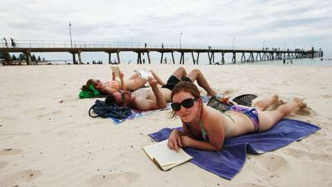 Two women and a man lying on the beach at Glenelg in South Australia.