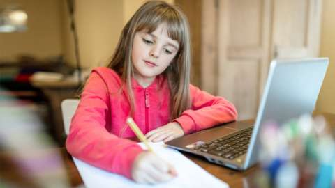 A girl doing school work with a laptop.