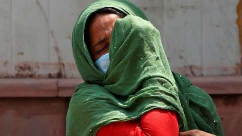 A woman mourns after her father died due to the coronavirus disease (COVID-19) outside a mortuary of a COVID-19 hospital in New Delhi, India, April 15, 2021.