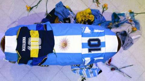 Coffin of Diego Maradona with flag of Argentina, football shirts and flowers