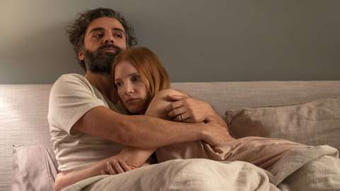 Jessica Chastain and Oscar Isaac cuddled together in a bed