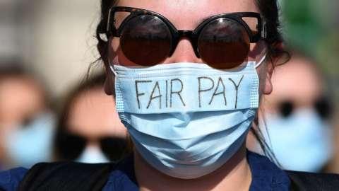 nurse with face mask and words 'fair pay'