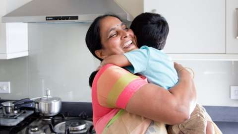 Woman in saree hugging her grandchild