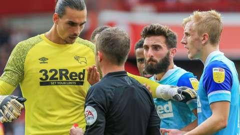 Derby players surround referee David Webb