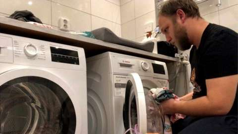 A man loading a washing machine