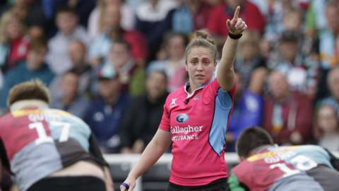 Sara Cox raises her hand to signal a refereeing decision