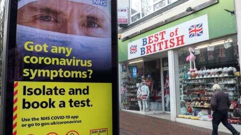 People walking past an NHS billboard