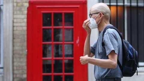 Man walking past phone box in mask