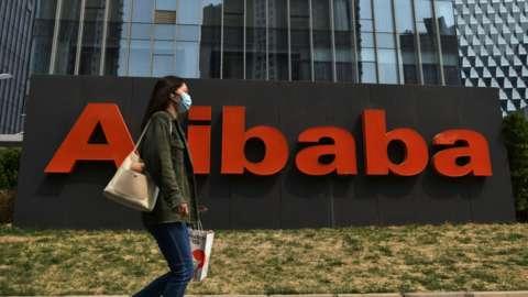 Woman walking past Alibaba sign at company headquarters.