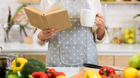 A woman reading a cookbook and preparing food