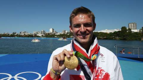 Pete Reed holds his gold medal