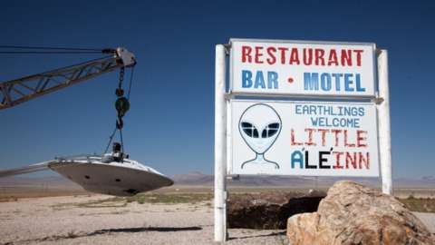 Sign for Little A'Le'Inn and flying saucer hanging from tow truck, Rachel, Nevada