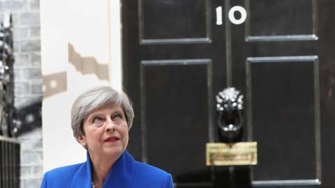 Prime Minister Theresa May pictured in front of 10 Downing Street on 9 June after she traveled to Buckingham Palace for an audience with Queen Elizabeth II following the General Election results.