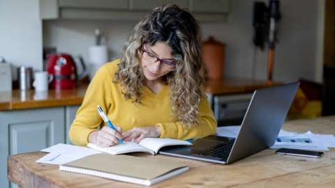 Woman working from home at kitchen table.