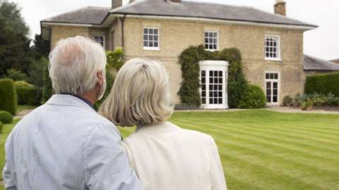 A photo of an older couple admiring house