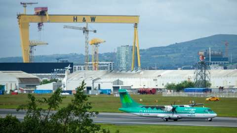 An Aer Lingus plane landing at Belfast City Airport with a Harland and Wolff shipyard crane in the background