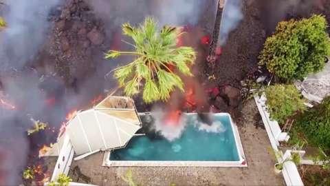 Lava pours into a swimming pool in La Palma