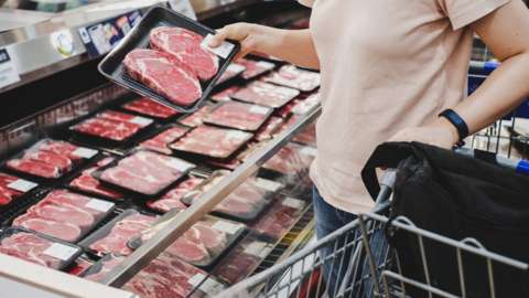 Woman shopping at meat section in supermarket.