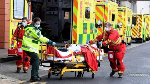 Ambulance workers assist a patient outside the Royal London Hospital in London