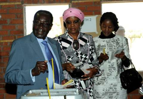 Zimbabwe President Robert Mugabe (L) casts his vote by his wife Grace and daughter Bona (R) at a polling booth in a school in Harare on July 31, 2013.