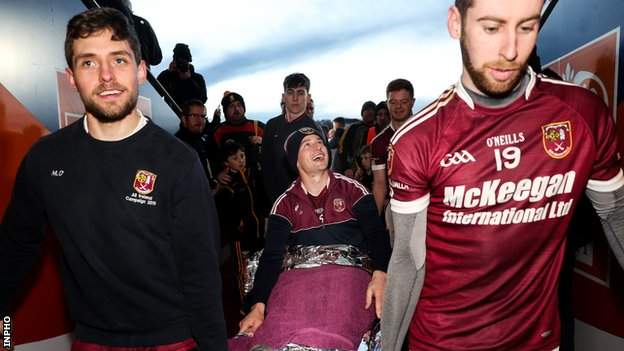 Arron Graffin is taken to the Cushendall dressing-room on a stretcher by team-mates Mark Donaghy and Stephen Walsh after Sunday's Ulster Club Final triumph