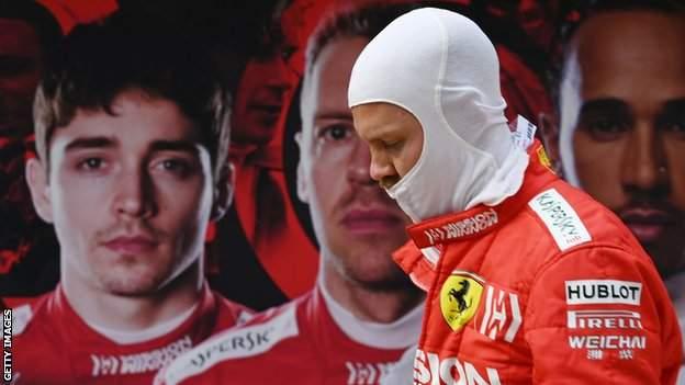 Sebastian Vettel walks past a poster of team-mate Charles Leclerc, Vettel and Lewis Hamilton
