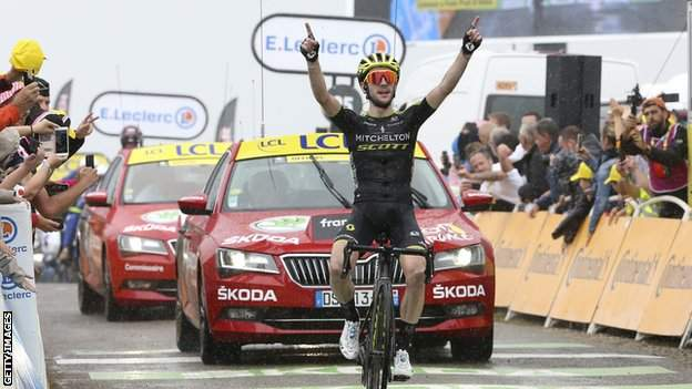 Simon Yates raises his hands in celebration after winning a stage of the 2019 Tour de France