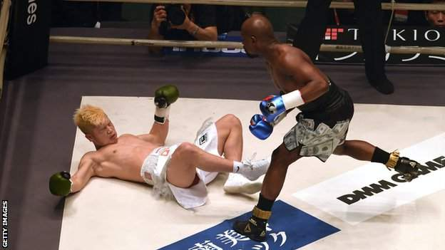 Japanese kickboxer Tenshin Nasukawa (left) is floored by former world champion boxer Floyd Mayweather (right) in an exhibition boxing match in Tokyo