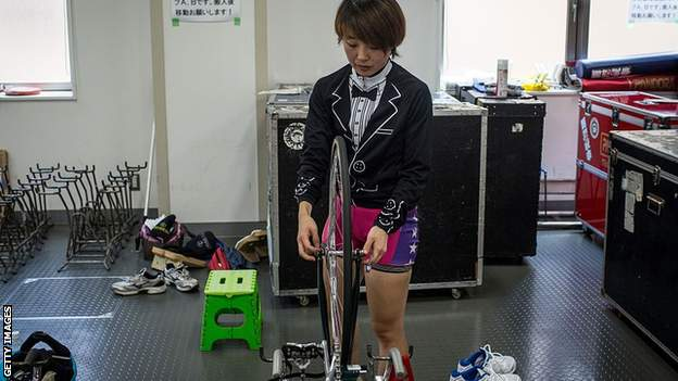 A female rider prepares her bike for inspection