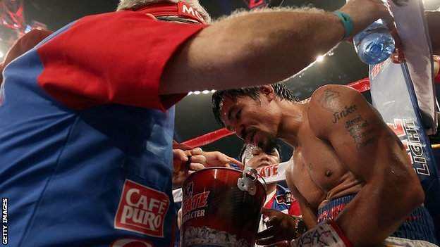 Manny Pacquiao spits into a bucket
